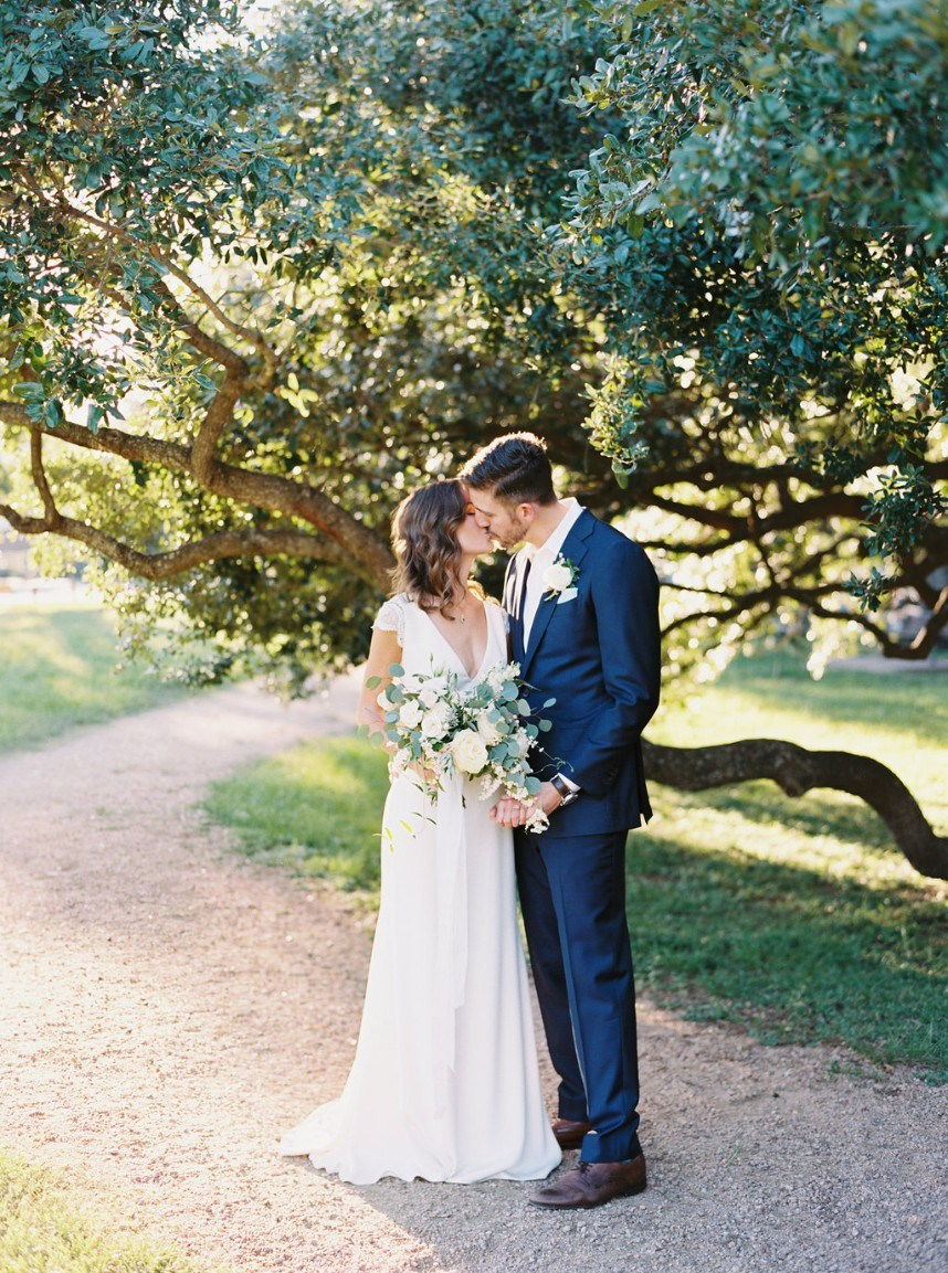 couple kissing under tree - tips for choosing a wedding photographer